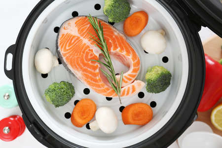 Salmon steak with garnish in multi cooker on table, top view