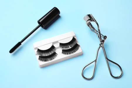 False eyelashes, curler and mascara on light blue background Reklamní fotografie