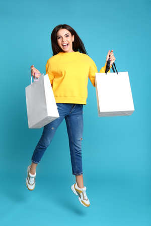 Happy young woman with paper bags jumping on blue background Foto de archivo