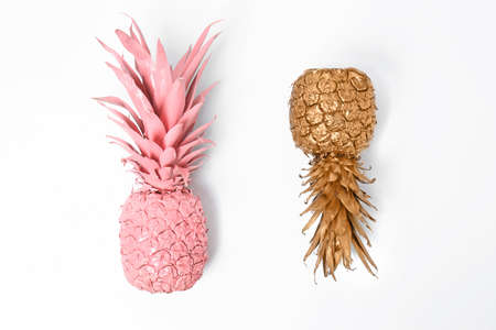 Shiny stylish gold and pink pineapples on white background, top view