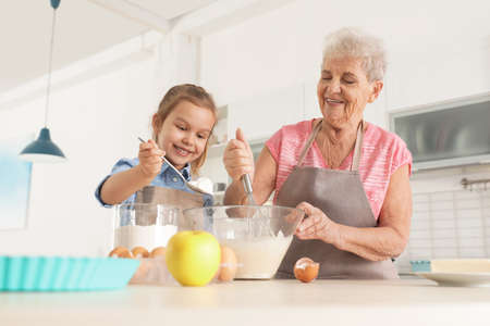 Cute girl and her grandmother cooking in kitchen Banque d'images