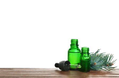 Bottles of essential oil, pipette and pine branch on table against white background