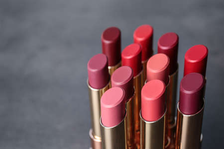 Set of bright lipsticks on grey background. Space for text