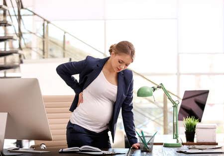 Jonge zwangere vrouw die pijn heeft tijdens het werken op kantoor