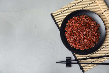 Flat lay composition with delicious cooked brown rice on grey table. Space for text