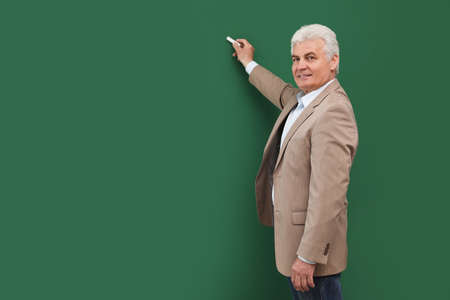 Portrait of senior teacher with chalk at green board, space for text Stockfoto