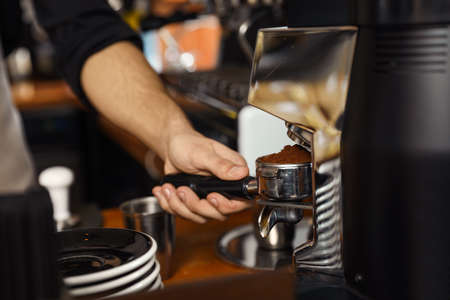 Barista pouring milled coffee from grinding machine into portafilter, closeup
