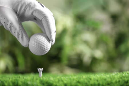 Player putting golf ball on tee against blurred background, closeup. Space for text