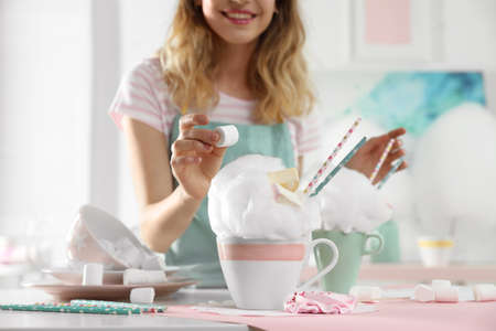 Young woman decorating cotton candy dessert with marshmallow at table, closeup