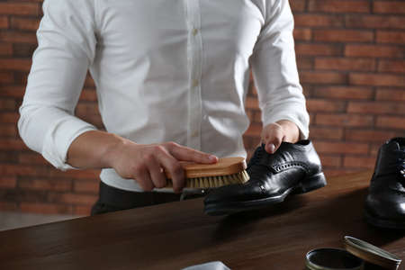 Man cleaning leather shoe at wooden table indoors, closeup