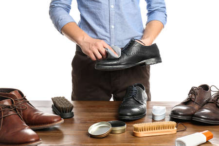 Man cleaning leather shoe at wooden table against white background, closeup
