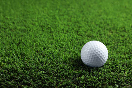 Golf ball on green grass. Space for text
