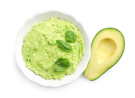 Bowl of tasty guacamole with basil and cut avocado on white background, top view