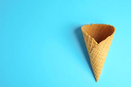Empty wafer ice cream cone on blue background, top view. Space for text