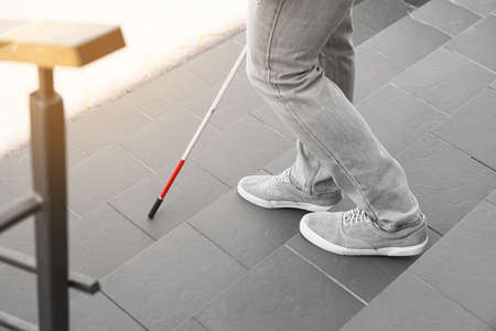 Blind person with cane going down stairs outdoors, closeup