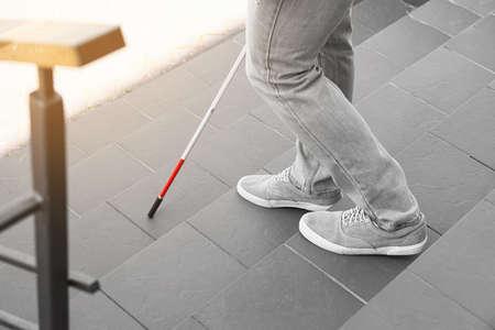 Ciego con bastón bajando escaleras al aire libre, primer plano
