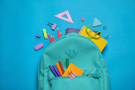 Stylish backpack with different school stationary on blue background, top view 版權商用圖片 - 127452670