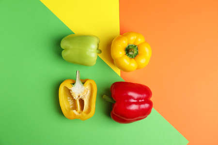 Flat lay composition with ripe bell peppers on color background