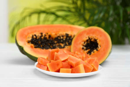 Fresh juicy papayas on white table against blurred background