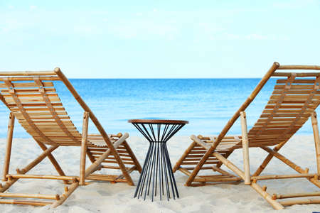 Empty wooden sunbeds and table on sandy shore. Beach accessories Standard-Bild