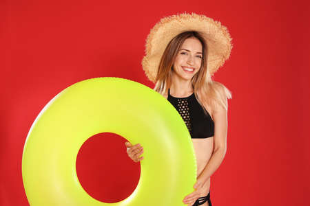 Beautiful young woman in stylish bikini with yellow inflatable ring on red background