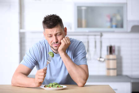 Portrait of unhappy man eating broccoli salad in kitchen