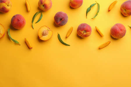 Flat lay composition with fresh peaches on yellow background. Space for text