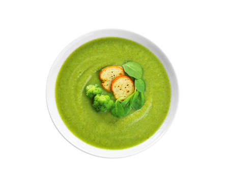 Bowl of broccoli cream soup with croutons on white background, top view