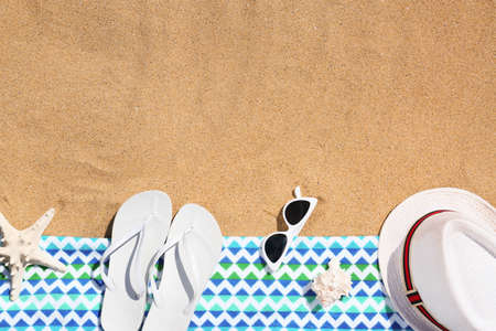 Flat lay composition with different beach objects on sand. Space for text