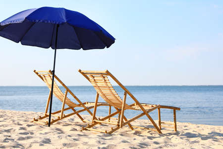 Empty wooden sunbeds and umbrella on sandy shore. Beach accessories Standard-Bild