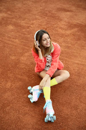 Happy stylish young woman with vintage roller skates and headphones sitting on tennis court