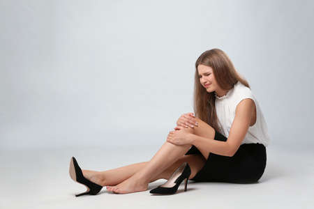 Full length portrait of businesswoman with knee problems sitting on grey background Imagens