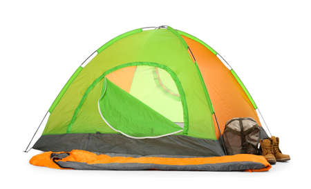 Comfortable colorful camping tent with sleeping bag and boots on white background