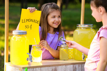 Cute little girl selling natural lemonade to kid in park. Summer refreshing drink