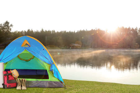 Colorful tent and camping equipment near lake