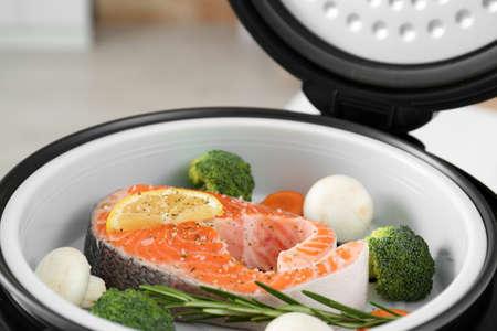 Salmon steak with garnish in multi cooker, closeup