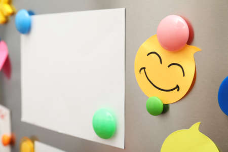 Sheets of paper and magnets on refrigerator door, closeup. Space for text