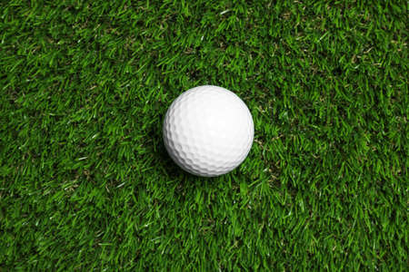 Golf ball on green artificial grass, top view 免版税图像
