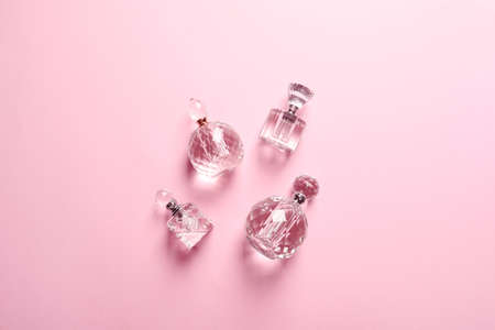 Flat lay composition with bottles of perfume on pink background