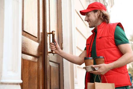 Mensajero masculino con pedido a la entrada. Servicio de comida a domicilio