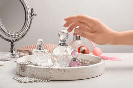 Woman reaching for crystal bottle of luxurious perfume on dressing table, closeup