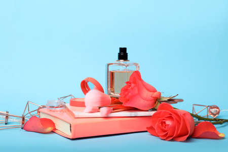 Composition with coral notebooks, flowers and perfume on light blue background