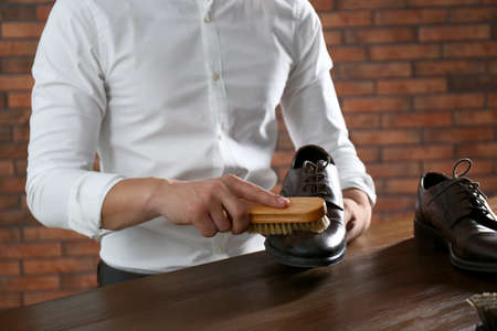 Man cleaning leather shoe at wooden table indoors, closeup Stock Photo