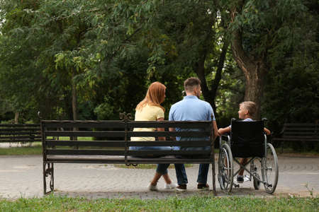 Boy in wheelchair with his family at park Stock Photo