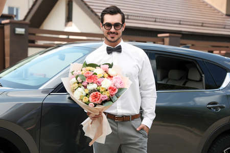 Young handsome man with beautiful flower bouquet near car outdoors
