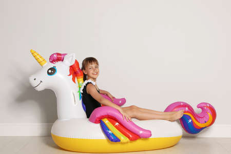Cute little girl on bright inflatable ring near light wall