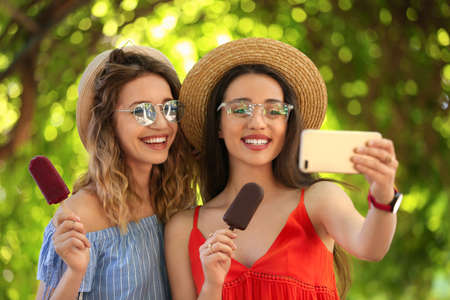 Happy young women with delicious ice creams taking selfie outdoors