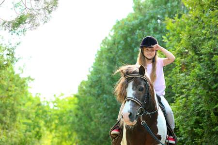 Nettes kleines Mädchen, das Pony im grünen Park reitet