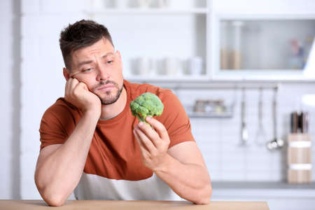Portrait of unhappy man with broccoli at table in kitchen