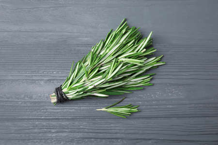 Bunch of fresh rosemary on color table, flat lay